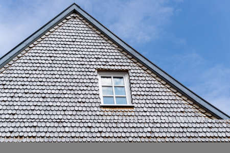 house gable: Gable of an old house with one window and gray shingles on the wall Stock Photo