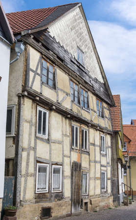 ruinous: Front of an old and in ruinous condition half-timbered house with missing shingles and ailing joist in Germany Stock Photo