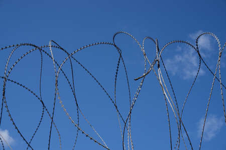 turned: Turned barbed wire with blue sky background Stock Photo
