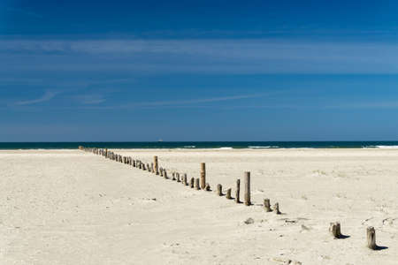 waters  edge: lead lonely beach with wooden posts to the waters edge