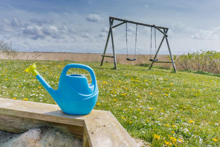 child s: Sandbox with small watering can with a child?,s swing in the background