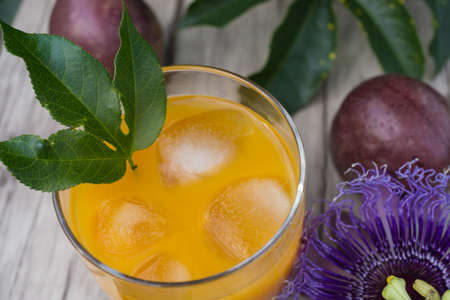 Fresh passion fruit juice with ice cubes and fresh fruits with view from above Stock Photo