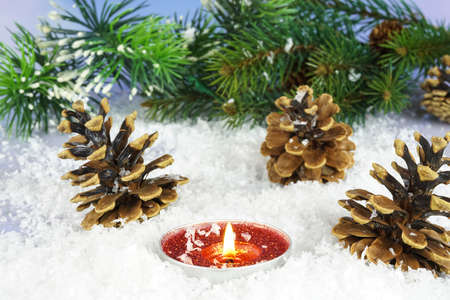 Red candle in the snow with pine cones and a pine branch in the background Stock Photo