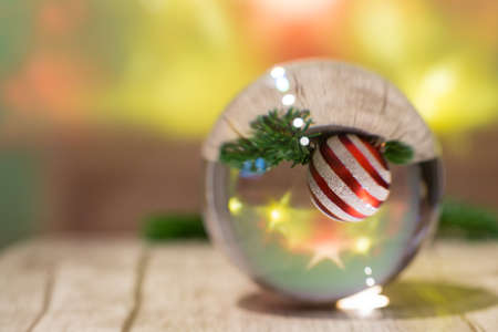 A glass sphere with a red white striped Christmas ball and pine branch inside and bright stars in green background, selected focus
