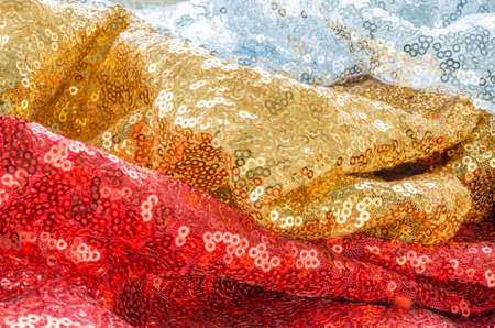 Gold, red and silver glittering fabric with sequins, laid in folds, copyspace
