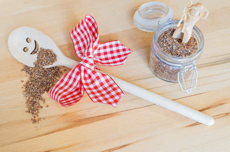 Wooden cooking spoon with smiling face and red white checkered bow, crushed linseed on the spoon and beside it, a mason jar with flaxseed and small wooden spoon, background of wood Stock Photo