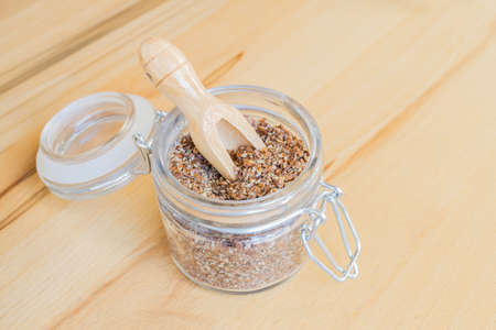 linum: A mason jar with crushed linseed and a small wooden spoon in it, background of wood Stock Photo