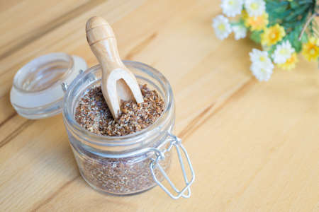 linum: A jar of julied linseed and a small wooden spoon in it and some summer flowers on the upper right edge of the picture, background of wood