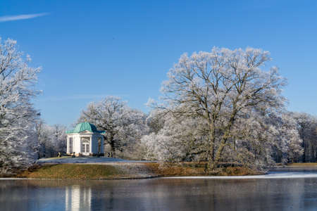 citypark: Winter landscape in a park in Kassel, Germany, light snow covered the trees and the lake is half-frozen, on the small Iceland in the lake is a small temple, sunshine and blue sky