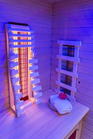 Infrared sauna with towel, blue illuminated