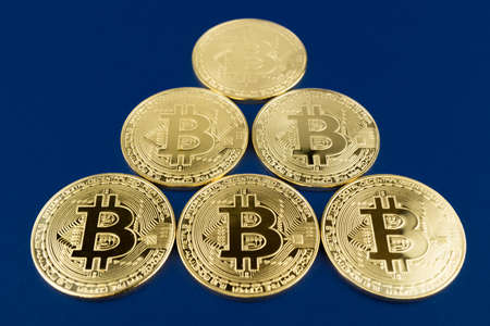 Bitcoins in pyramid on blue background