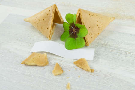 Broken fortune cookie with four-leaf clover Stock Photo