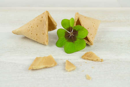 Broken fortune cookie with blank label and four-leaf clover, wooden background