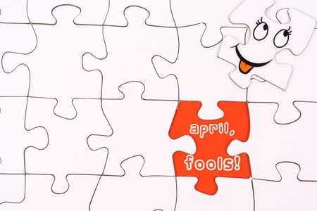 Puzzle pieces with funny faces and the words April fools