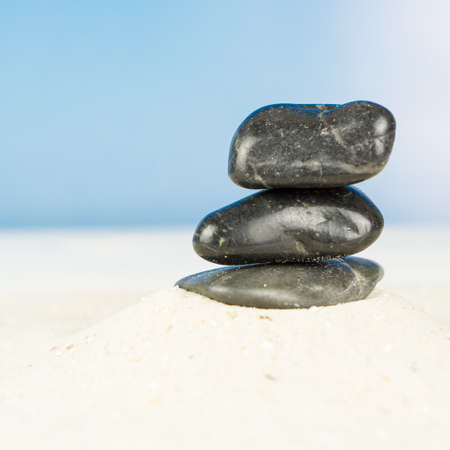 Three black stones on the beach Banco de Imagens - 97330091