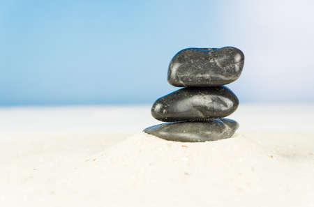 Three black stones on the beach Banco de Imagens - 97330094