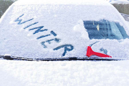 Scraping snow from the window of a car Stok Fotoğraf
