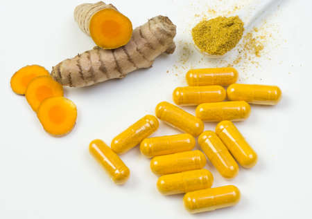 Turmeric root with yellow capsules and a spoonful of curcuma powder