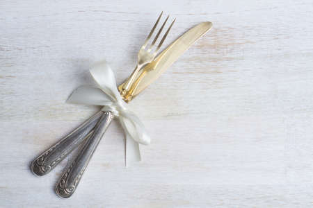 Silverware with white ribbon on white wooden background