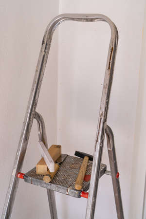Ladder with folding rule and hammer