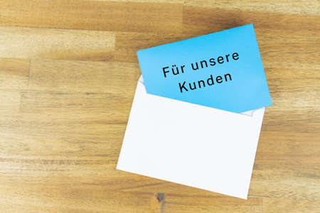 Envelope with a blue note with the german words FOR OUR CUSTOMERS 写真素材