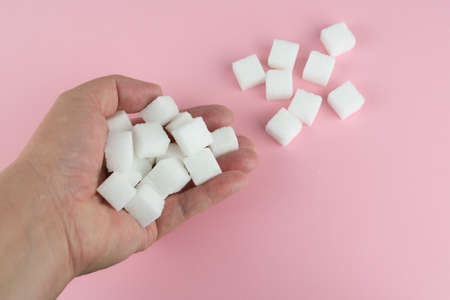 Sugar cubes holding in hand, pink background with copy space
