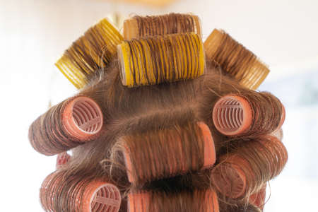 Woman's head with colorful curlers