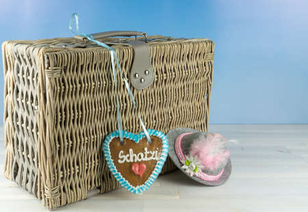 Old wicker basket with a gingerbread heart and the German word for sweetie and a bavarian hat on wooden table, blue sky background Standard-Bild