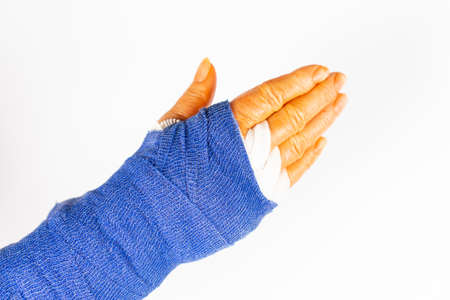 freshly operated hand with blue bandage and disinfectant orange fingers