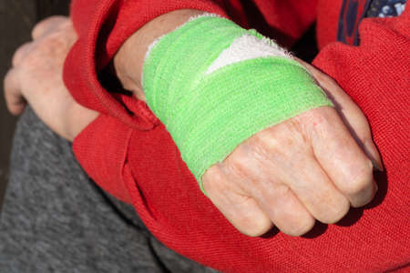 Woman in red sweater with a bandaged hand in green