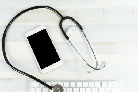 A cellphone with a stethoscope and a computer keyboard on a wooden table Stock fotó