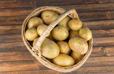A wicker basket with fresh potatoes on a wooden table, view from above Banco de Imagens