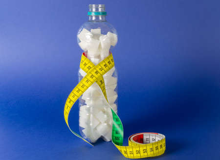 A plastic bottle with sugar cubes and a measuring tape, blue background and copy space