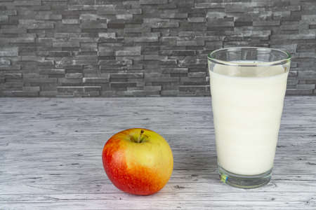 A glass of fresh milk and an apple fruit, black stone background and copy space