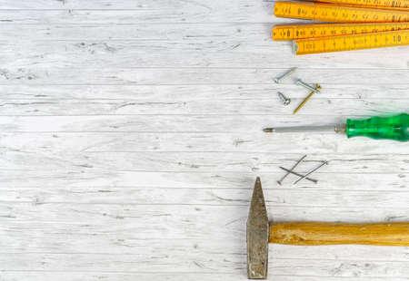 Handwerkzeuge auf weißem Holzhintergrund, Hammer mit Nägeln und Zollstock, daneben ein Schraubendreher mit verschiedenen Schrauben und Zangen Standard-Bild