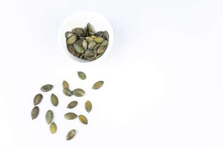 A cup with pumpkin seeds on white background with copy space Zdjęcie Seryjne
