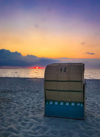 Traditional Baltic beach chair at the German Baltic Sea coast in the sunset Zdjęcie Seryjne