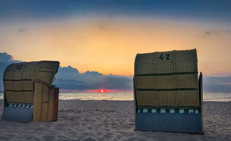 Two traditional Baltic beach chairs at the German Baltic Sea coast in the sunset