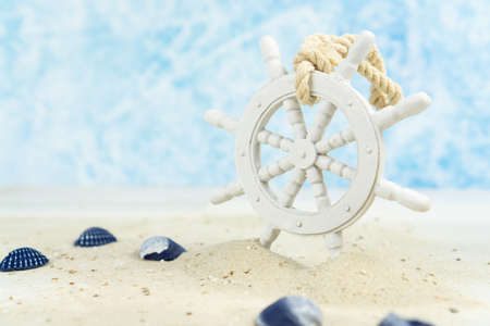 Maritime background with sand, shells and an old white wooden wheel