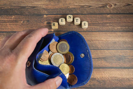 Hand holds a blue wallet with euro coins, wood background with the german word for pension