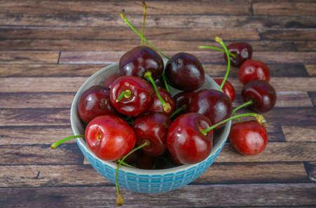 Fresh sweet cherries in a cup, dark brown wood background with copy space Zdjęcie Seryjne