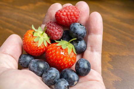 Hand with fruits, strawberries, raspberries and blueberries