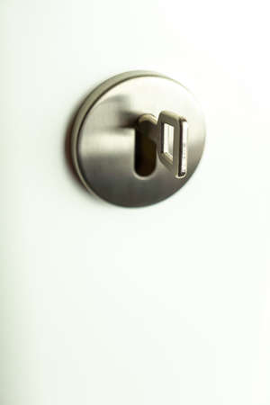 Key in a round silver keyhole in a white door, copy space