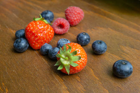 Strawberries, raspberries and blueberries lie on a wooden table