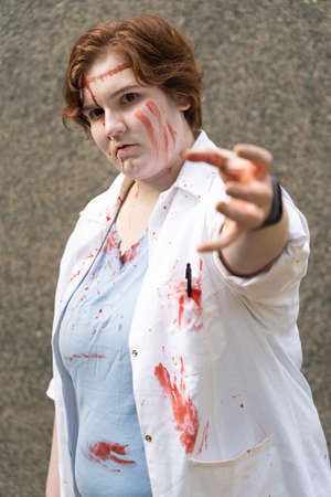 Young bloodied woman in white coat
