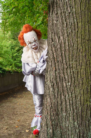 Dangerous horror clown looks out from behind a tree 版權商用圖片