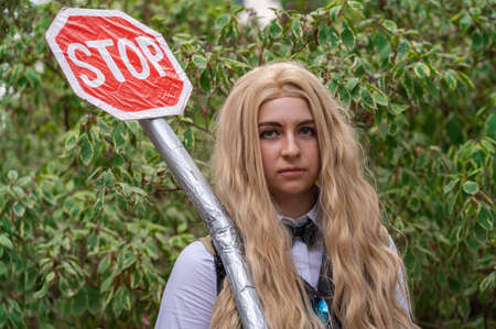 Young blond girl with a red stop sign Zdjęcie Seryjne