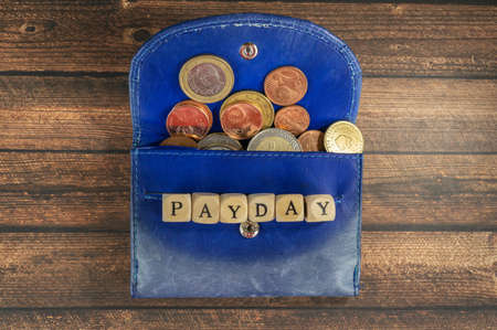 Blue wallet with euro coins and the word payday, wood background and copy space