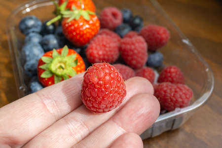 Woman is picking out a raspberry from a bowl of raspberries, blueberries and strawberries