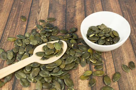 A wooden spoon and a white bowl with many pumpkin seeds, wooden background